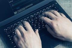 黑客手在膝上型计算机的工作 第一人景色 免版税库存图片
