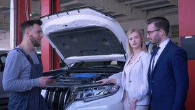 客服在汽车车间,专业技术员与开放敞篷咨询关于残破的汽车的家庭客户 股票录像