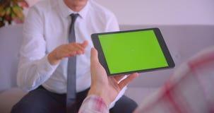 客服服务管理人员特写镜头画象谈话与客户有绿色色度屏幕的藏品片剂在办公室 股票视频