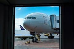客机在等候离开的停车空间的机场站立的过程为飞行做准备  免版税库存照片