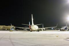 客机的背面图在机场围裙的在冬天晚上 库存图片