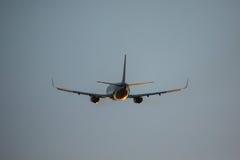 客机飞行在从机场的起飞跑道日落的 从机场的平面离开 免版税图库摄影