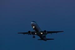 客机飞行在从机场的起飞跑道日落的 从机场的平面离开 免版税库存照片