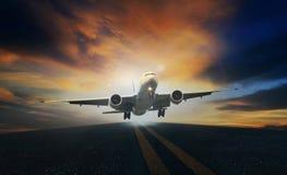 客机从跑道起飞反对美丽的暗淡的sk 免版税图库摄影