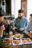 客栈饮用的啤酒和吃食物的人 库存图片