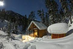 客舱房子瑞士山中的牧人小屋在有雪的冬天森林里在轻的月亮和 免版税图库摄影
