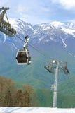 客舱缆索铁路在反对绿色森林和山背景的一条多雪的滑雪轨道上  库存照片