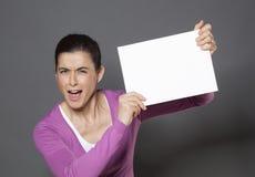 宣布在培养的充满活力的30s妇女白色插入物的一个公告在她前面 免版税库存图片