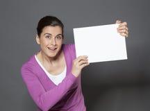 宣布在培养的精力充沛的30s妇女白色插入物的一个公告在她前面 库存图片