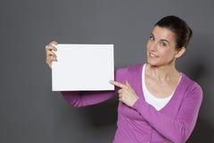 宣布在拿着的美丽的30s妇女白色插入物的一个公告在她前面 库存图片