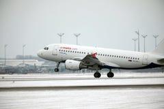 宣扬在慕尼黑机场,在跑道的雪的马耳他空中客车A319-100 9H-AEJ着陆 免版税库存照片