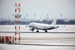 宣扬在慕尼黑机场,在跑道的雪的马耳他空中客车A319-100 9H-AEJ着陆 免版税库存图片