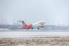 宣扬马耳他离开从多雪的跑道的空中客车A320-200 9H-AEQ 免版税图库摄影
