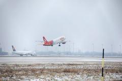 宣扬马耳他离开从多雪的跑道的空中客车A320-200 9H-AEQ 库存照片
