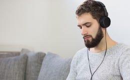 年轻室内人听的放松音乐 免版税库存图片