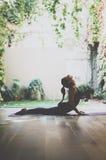 室内华美的少妇实践的瑜伽画象  在类的美丽的女孩实践眼镜蛇asana 平静和放松 免版税库存照片