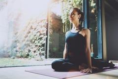 室内华美的少妇实践的瑜伽画象  在类的美丽的女孩实践asana 平静和放松 免版税库存图片
