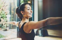 室内华美的少妇实践的瑜伽画象  美丽的女孩实践战士光asana 平静和放松 免版税库存图片
