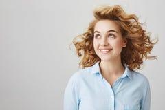 室内射击在有风阳台的正面有吸引力的欧洲女性身分和看在旁边与微笑,当卷曲时 免版税库存照片