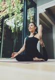 室内愉快的少妇实践的瑜伽画象  在类的美丽的女孩实践放松asana 平静和 免版税库存照片