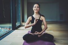 室内愉快的少妇实践的瑜伽画象  在类的美好的微笑的女孩实践莲花坐 平静 免版税库存图片