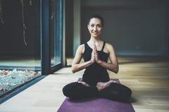 室内愉快的少妇实践的瑜伽画象  在类的美好的微笑的女孩实践莲花坐 平静 免版税库存照片