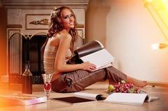 室内杂志读取被射击的坐的妇女 免版税库存图片