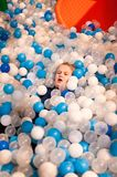 室内游乐园的女孩在塑料球中 免版税库存照片
