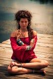 室外一个冥想的瑜伽的位置的妇女 免版税库存照片