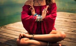 室外一个冥想的瑜伽的位置的少妇 免版税库存图片
