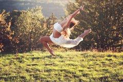室外一个困难的跃迁的美丽的体操运动员 免版税库存照片