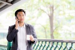 室外一个确信的商人谈的手机的电话的画象 免版税图库摄影