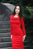 室外一件性感的红色的礼服的美丽的女孩 免版税库存照片