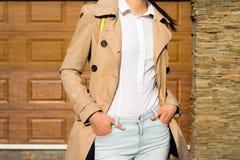 室外一件米黄外套、的蓝色牛仔裤和白色的衬衣的苗条女孩 免版税图库摄影