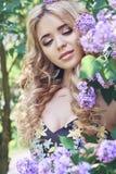 室外丁香围拢的时尚美丽的少妇开花夏天 春天开花淡紫色灌木 白肤金发的女孩的画象 免版税库存图片