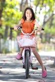 室外亚洲逗人喜爱的小女孩骑马的自行车 免版税库存照片