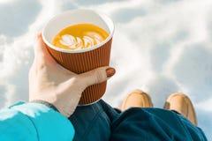 室外冬时,有咖啡的妇女手,雪背景  库存照片