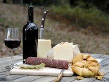 室外吃用面包、乳酪、香肠和红葡萄酒 免版税图库摄影