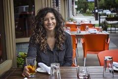 室外咖啡馆小餐馆的俏丽的妇女 免版税图库摄影