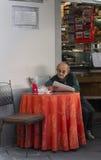 室外咖啡馆的老人,读报纸, 2014年10月22日,卢卡,意大利 库存图片