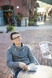 室外咖啡馆的年轻亚裔人 免版税图库摄影