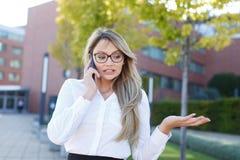 室外困惑的女实业家叫由电话,混乱 免版税图库摄影