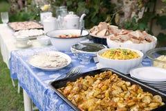室外夏天婚礼聚会事件承办酒席宴会用食物和典雅的桌设置 免版税库存图片