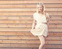 室外夏天肉欲的时尚画象美丽的年轻白肤金发的妇女举站立在背景的一件白色礼服的边缘  免版税图库摄影