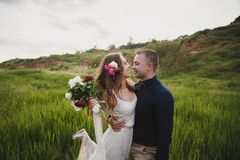 室外婚礼、时髦的愉快的微笑的新郎和新娘是拥抱和看彼此 在亲吻前的片刻 免版税库存照片