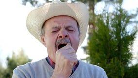 室外帽子打呵欠的身分的老人 股票录像