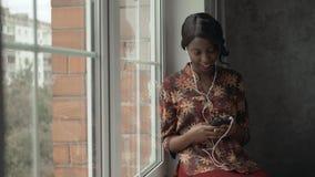 室外年轻黑人妇女听的音乐旅行看起来窗口,沉思-周道,想法的未来,音乐 股票视频