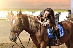 室外幼小俏丽的深色的骑乘马 免版税库存图片