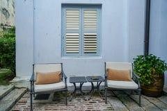 室外庭院家具、灰色金属躺椅和旁边桌在蓝色大厦墙壁前面有传统窗口的 库存图片