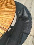 室外弯曲的长凳的阴影在强的光的 免版税库存照片